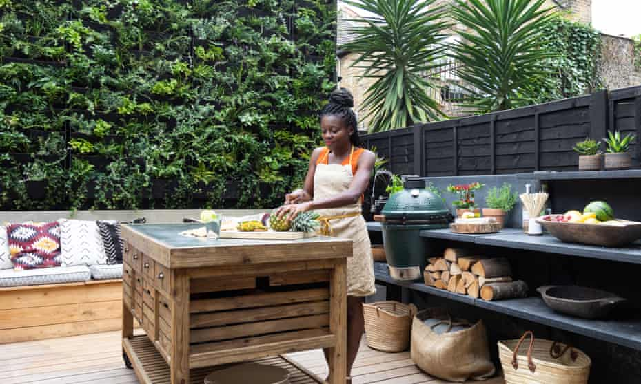 Carine Ottou chopping a pineapple at the kitchen island in the garden