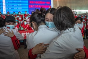 Medical workers from The First Bethune Hospital of Jilin University hug their Wuhan colleagues at the airport as they prepare to leave