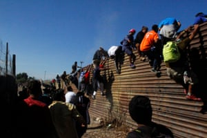 Migrants climb the border fence between Mexico and the United States in an attempt to cross into the US side of the border on Sunday.