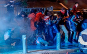 Protesters shelter as police use water cannon during clashes