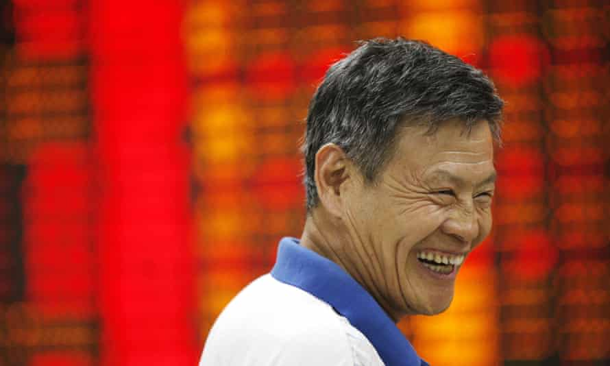 An investor smiles while observing stock market figures at a stock exchange in Huaibei, Anhui Province of China. Chinese shares rebounded again Friday as a result of heavy government intervention.