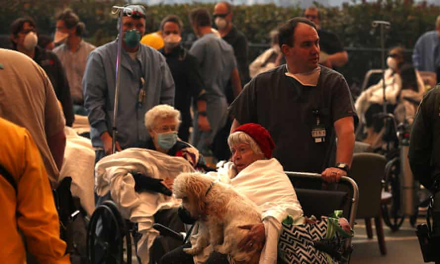 Hospital workers and first responders evacuate patients from the Feather River Hospital in Paradise, California.