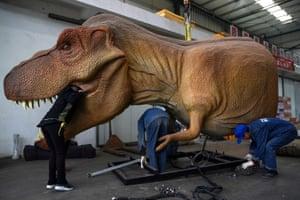 Workers service an animatronic dinosaur in Zigong, China