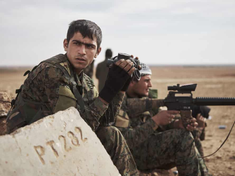 Using binoculars and scopes, SDF fighters watch for Isis infiltration and suicide vehicles on the frontline in Raqqa.