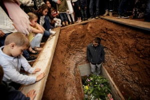 A relative reacts during the burial of Rhonita Miller and her children Howard, Kristal, Titus, and Teana, who were killed by unknown assailants in Le Barón, Mexico.