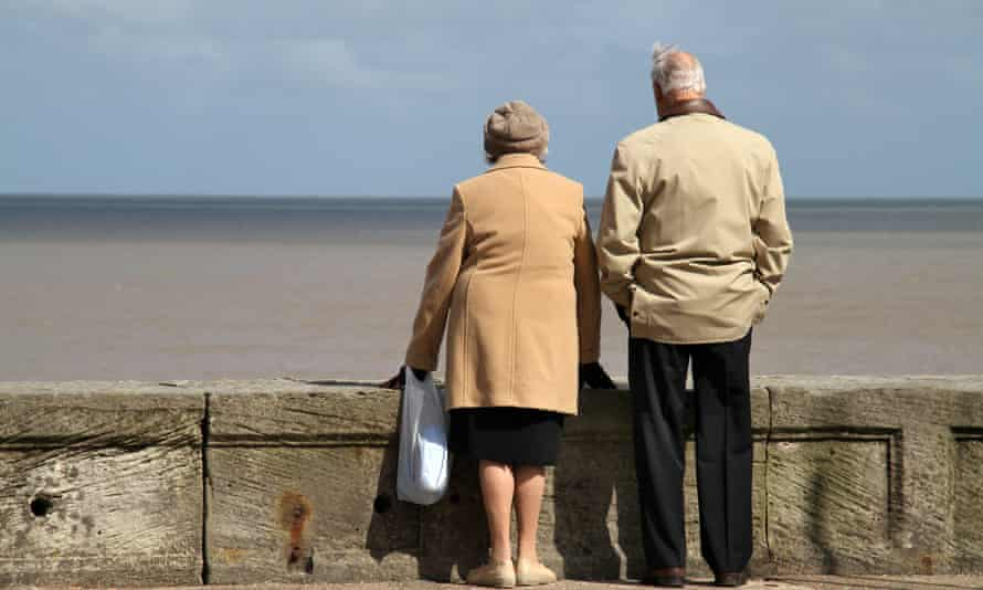 Old couple on sea wall looking out at horizon