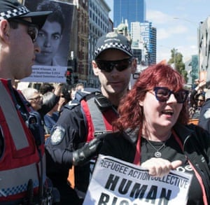 Christina Coombe, who died in May 2019, at a rally holding a sign from the Refugee Action Collective, with two police officers.