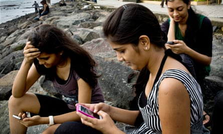 young women check their smartphones by the beach in Mumbai, India