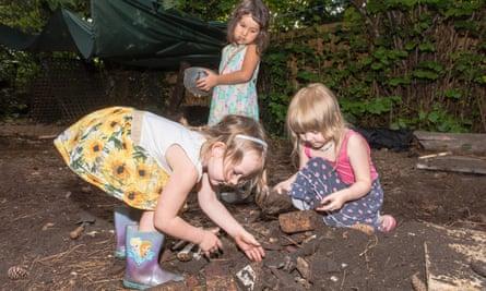 Children play in a forest school garden in Cambridge.