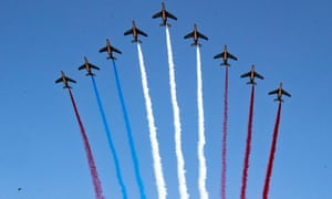 Nine planes in the sky, with coloured trails behind them: one of the red trails should be blue