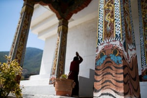 A man prays at the Memorial Stupa in capital Thimphu. All columns surrounding the stupa feature tigers.