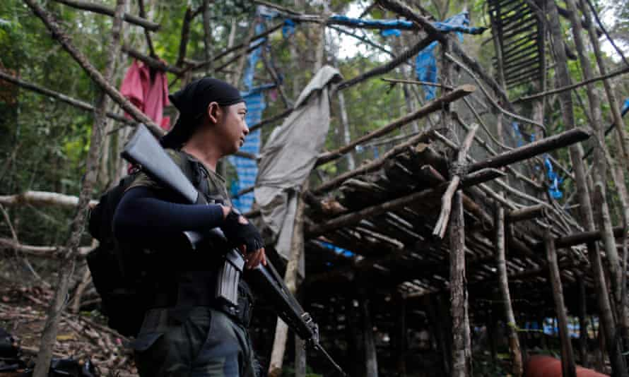 An armed Royal Malaysia Police stands guard in an abandoned camp in which graves are found at Wang Burma hills at Wang Kelian, in Malaysia.