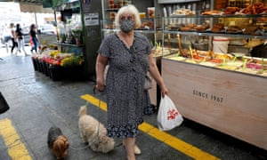 A woman wears a face mask as she walks with her dogs in a main market in Jerusalem 16 July 2020.