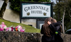 Students from Holy Trinity College leave floral tributes outside Greenvale hotel in Cookstown, County Tyrone.