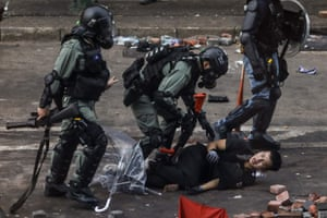 Armed police pin a protester to the ground as they attempt to arrest him