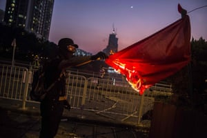 A protester sets fire to the Chinese national flag in the Sha Tin district.