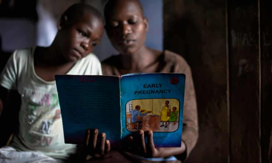 Young women read an educational book at an adolescent youth centre in Uganda