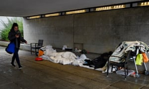 A young woman passes makeshift beds for homeless people in an underpass near the main shopping area in Milton Keynes.