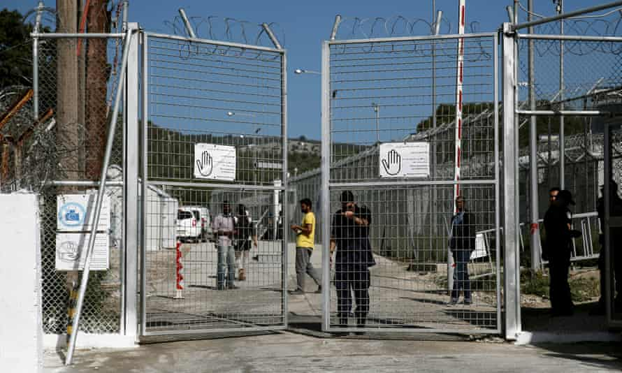A police officer closes the gate of the Moria detention centre in Greece.
