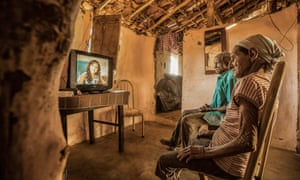 A couple in Brazil watch a television programme to improve literacy.