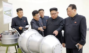 Kim Jong-un inspects a device, or perhaps a model of a bomb, in front of a diagram suggesting its size may be small enough to fit into an ICBM. Photograph: KCNA/EPA