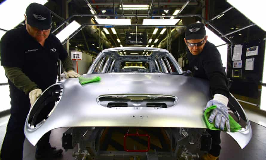 Workers inspect a Mini bodyshell for imperfections