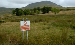 An MoD warning sign, with the disputed fells in the background.