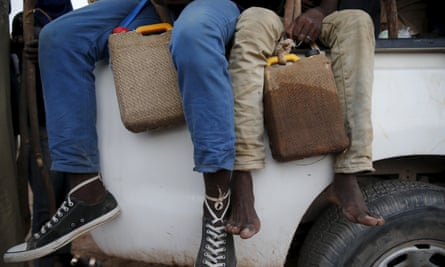 Migrants hold water containers wrapped in cooling wet sacks to as they sit on the back of an overcrowded truck at a local immigration transit centre in the desert town of Agadez, Niger