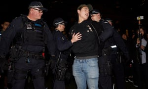 Police detain a man during a rally at the State Library in Melbourne