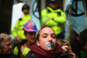 A protester with tape over their mouth with 'Silence is deadly' written on it