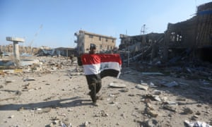 A member of the Iraqi security forces holds his national flag on 28 December after the recapture of the city of Ramadi