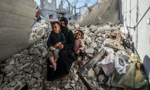 A woman with her children in the rubble of a building in the Jarabulus district