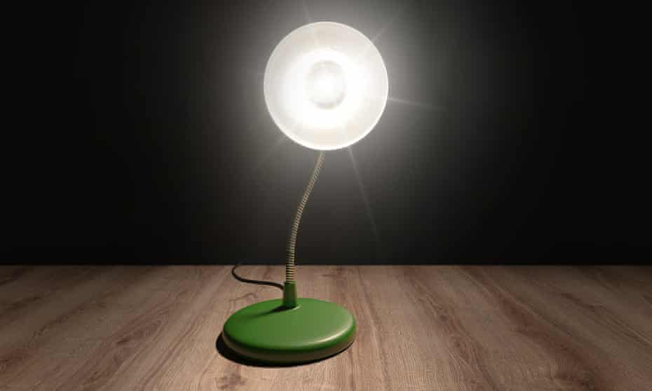 A desktop lamp in a dark room pointing brightly at the viewer.