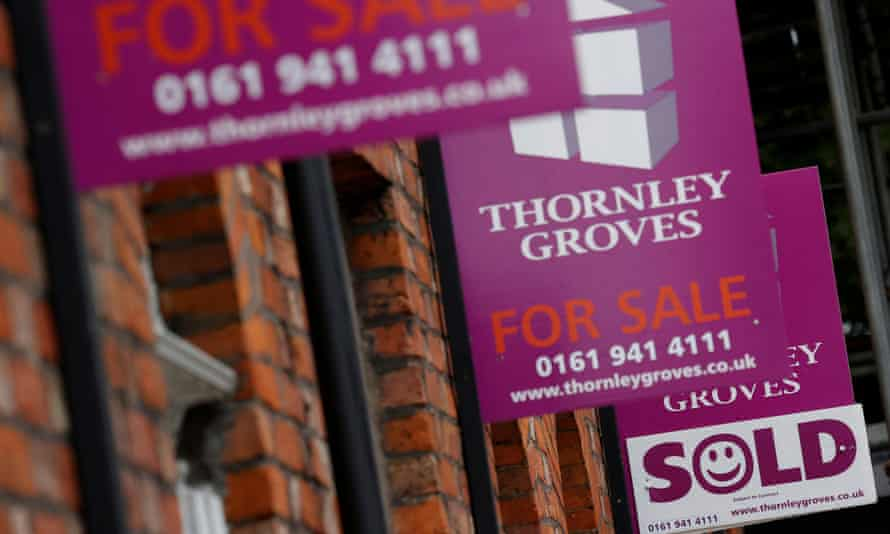 Real estate agents' boards outside a row of terraced houses in Manchester