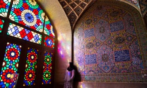 A young women rests next to a glowing stain-glassed window in Shiraz, Iran.