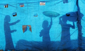 Silhouettes of Iraqi children as they collect water from a tank at the Al-Khazir camp