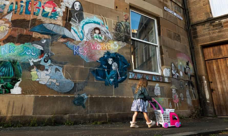 Child with toy pram in Edinburgh street.
