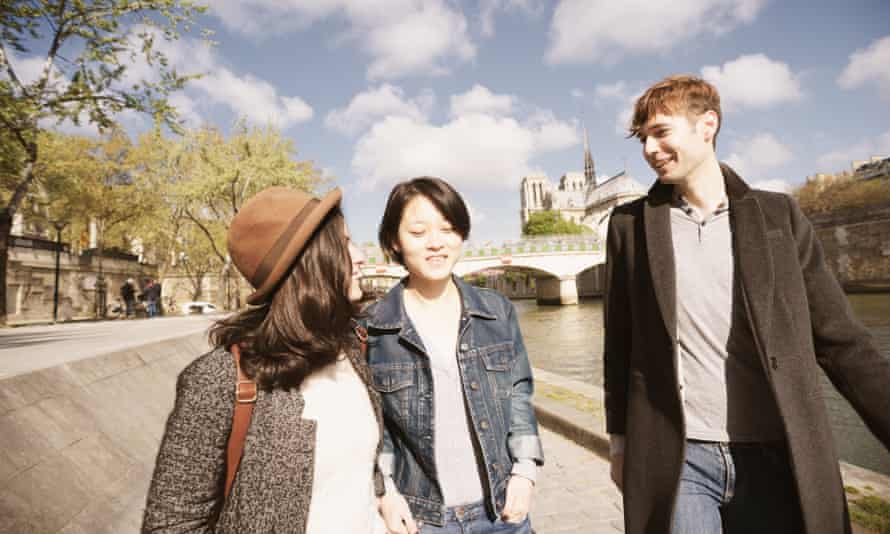 Three young friends taking a promenade in Paris, France along the River Seine, with Notre Dame cathedral in the background