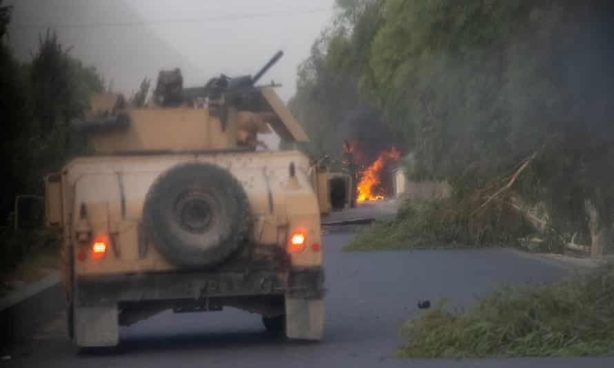 A column of armoured cars; the lead vehicle is on fire.