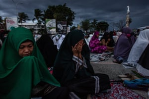 """Trotter: """"These moving scenes were captured during a mass prayer on Talise beach following the deadly earthquake and tsunami that hit the island of Sulawesi. The photographer focused on documenting the emotional impact of the disaster and how the community came together to mourn during the ongoing search efforts to locate 5,000 missing people. This impactful image continues to be a reminder of the suffering of those who have their lives turned upside down by natural disasters around the world'"""