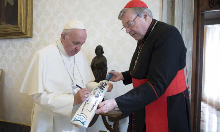 Pope Francis signs a cricket bat given to him by Cardinal George Pell at the Vatican in October 2015.