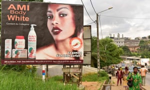 Colorism is not just an American phenomenon.. Pedestrians walk past a hoarding advertising a skin-whitening cream in Abidjan, Ivory Coast.