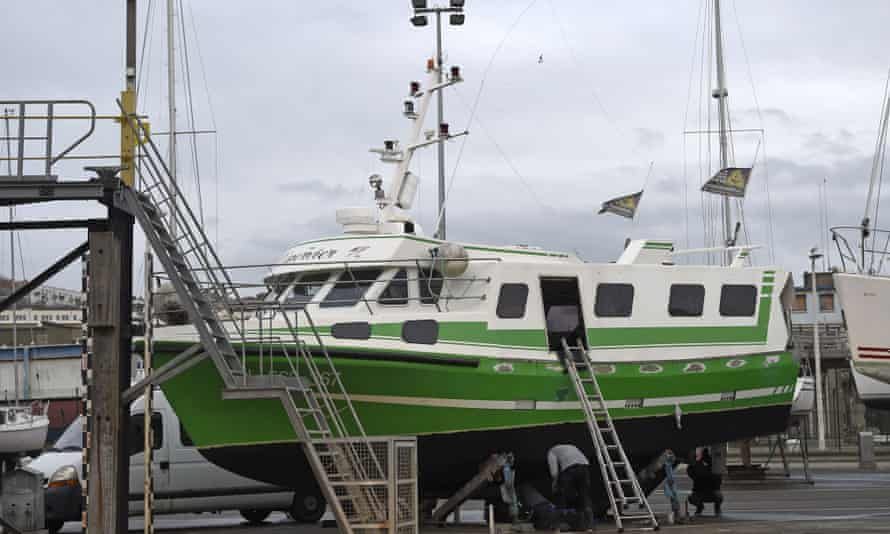 French workers repair L'Epervier, a boat that was stolen and damaged by migrants who tried to cross the Channel, in Wissant, northern France.