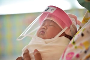 A newborn baby wears a face shield at Praram 9 Hospital in Bangkok, Thailand