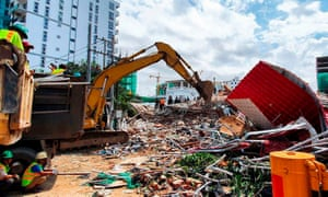 Rescue workers use an earthmover to clear debris after an under-construction building collapsed in Sihanoukville, with fears dozens more may be buried in the rubble.