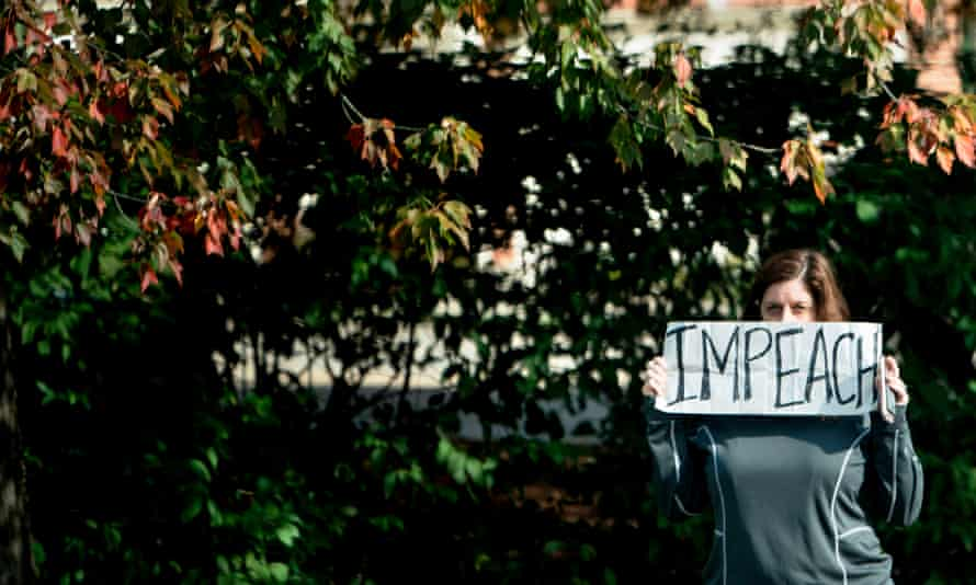 """A protester holds an """"impeach"""" sign outside the Trump National Golf Course as the presidential motorcade arrives."""