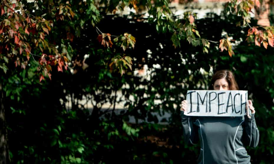 A protester holds an 'impeach' sign outside the Trump National golf course as a motorcade with Donald Trump arrives in Sterling, Virginia, on 28 October 2017.