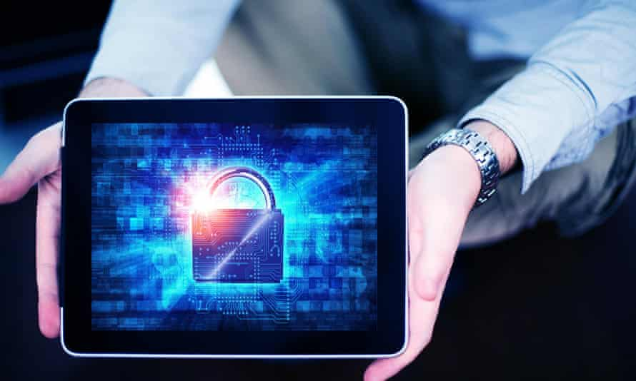 A man holds an electronic tablet with a padlock depicted on the screen