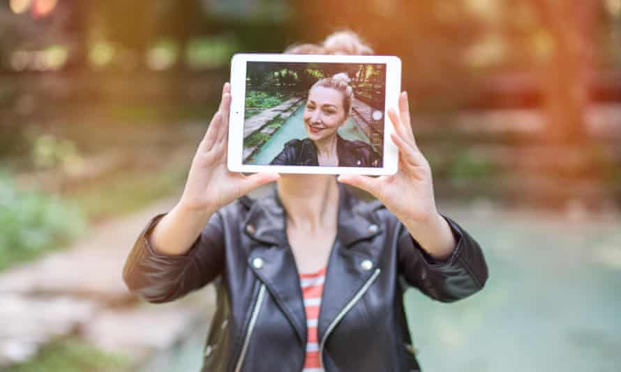 In the frame: beautiful young woman taking a selfie with her tablet. focus on the screen. graded with a flare, in instagram styleH466CX beautiful young woman taking a selfie with her tablet. focus on the screen. graded with a flare, in instagram style