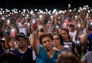 People hold up their phones during a vigil after a shooting left 20 people dead at the Cielo Vista Mall Walmart in El Paso, Texas on 4 August 2019.